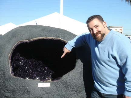 Jasun pointing to Calcite in large Amethyst Geode in front of the Inn Suites